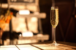Shot of the champagne glass on a wooden table. Sunlight and bubbles.