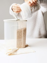 Shot of the female hands pouring cereals into a two-compartment container. Plastic tableware is standing on the kitchen towel. Kitchen towel, white table and container are on the gray background.