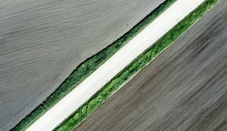 Shot of the field from drone. Farmers field. Road between fields. Background or texture