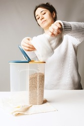 Shot of the girl pouring cereals into a two-compartment container. Plastic tableware is standing on the kitchen towel. Kitchen towel, white table, girl and container are on the gray background.