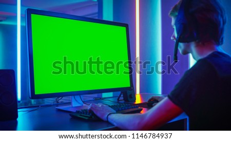 Shot of the Professional Gamer Playing on His Personal Computer with Green Screen Mock-up Template. Room Lit by Neon Lights in Retro Arcade Style. Online Cyber e-Sport Internet Championship. #1146784937