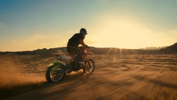 Shot of the Professional Motocross Driver Riding on His FMX Motorcycle on the Extreme Off-Road Terrain Track. Blur motion.