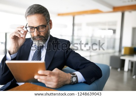 Shot of thinking financial advisor businessman working in office. #1248639043