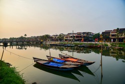 Shot of three empty passenger fishing boats sitting on calm, glassy river waters in the early morning as dawn is stretching across the sky in Hoi An Vietnam
