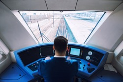 Shot of train cockpit interior with driver sitting and driving train.