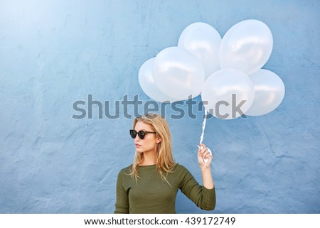 Shot of trendy young female with sunglasses holding balloons and looking away against blue wall. #439172749