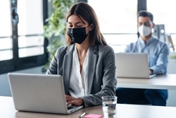 Shot of two attractive business partners wearing a hygienic face mask while working with laptops in the coworking space. Social distancing concept.