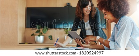 Shot of two businesswoman working together on digital tablet. Creative female executives meeting in an office using tablet pc and smiling.