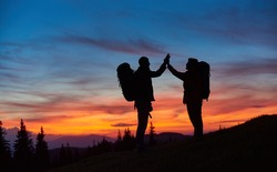 Shot of two hikers high fiving standing on top of a mountain with their backpacks copyspace beautiful sunset on the background anonymous achievement gesture celebrating hiking silhouette.
