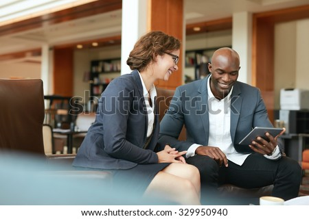 Shot of two people looking at something on a touchscreen computer. Smiling business people using digital tablet while sitting at coffee shop.