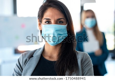 Shot of two pretty business women wearing a hygienic face mask while looking at camera in the coworking space. Social distancing concept.