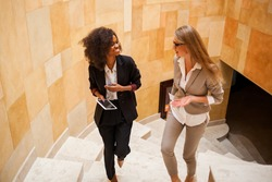 shot of two smiled businesswomen going upstairs. Women wearing suits. One woman is black.