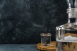 Shot of vodka on table against black wall. Decanter is in foreground in blur. Free space for text