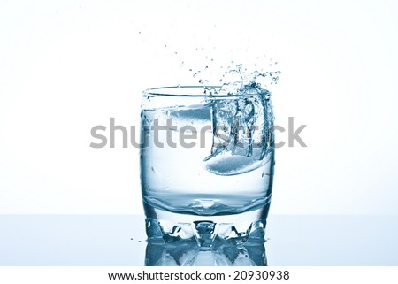 shot of water splashing from ice being dropped in a glass.