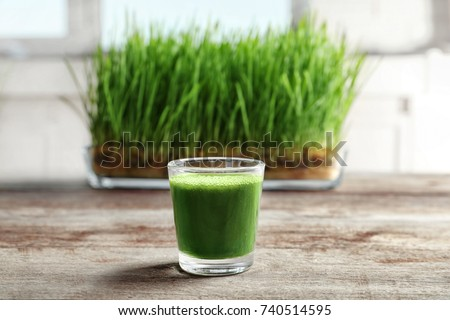 Shot of wheat grass juice on wooden table