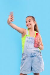 Shot of young brunette girl wearing  denim overalls shorts standing with a phone and with a bottle of water. She takes a selfie. Vacation and reacriation concept