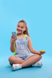 Shot of young brunette smiling girl teenager wearing  denim overalls shorts sitting in lotus position and looking at the phone. Vacation and reacriation concept