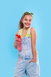 Shot of young brunette smiling girl wearing  denim overalls shorts and green sunglasses standing with  a red bottle of water.  Vacation and reacriation concept