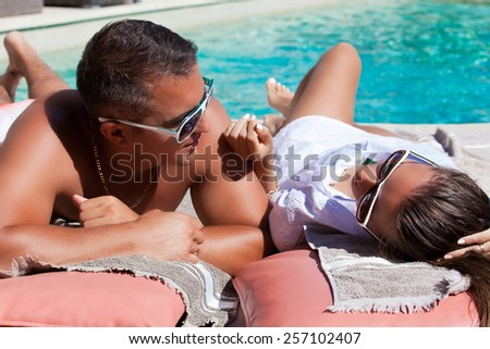 Shot of young couple relaxing at the luxury poolside, at travel spa resort pool. Couple in love, summer luxury vacation in Europe. Travel holidays concept.