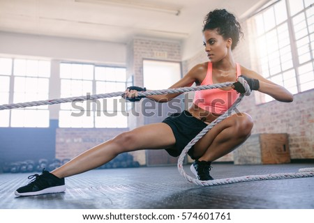Shot of young fitness female exercising with rope at a gym. Young woman pulling rope at gym.