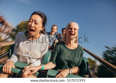 Shot of young friends cheering and riding roller coaster at amusement park. Young people having fun on rollercoaster.