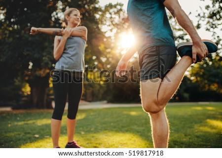 Shot of young man and woman stretching in the park. Young couple warming up in morning.