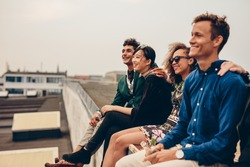 Shot of young men and women sitting together on rooftop. Mixed race friends relaxing on terrace.
