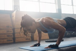 Shot of young woman doing push-ups at the gym. Muscular female doing pushups on exercise mat at gym. Female exercising on fitness mat at gym.