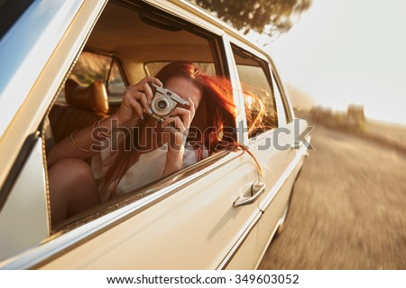 Shot of  young woman taking photos while sitting in a car. Female capturing a perfect road trip moment. Foto stock ©