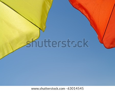 shot taken under a green and orange sun umbrellas against the perfect blue sky