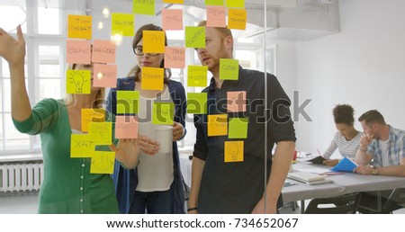 Shot through glass of bright stickers on glass wall and young creative people behind collaborating on new plan ideas.