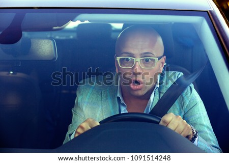 Shot through windscreen of car of man in glasses driving and having accident looking extremely shocked holding steering wheel and looking away.
