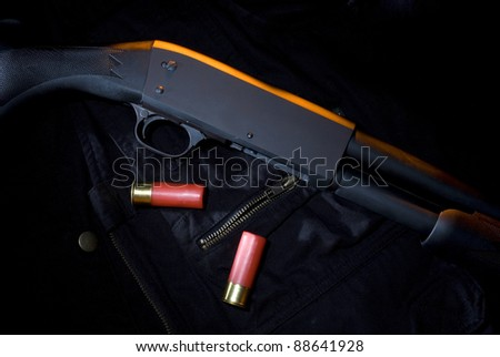 Shotgun on a tactical vest with ammo and an orange gel from above