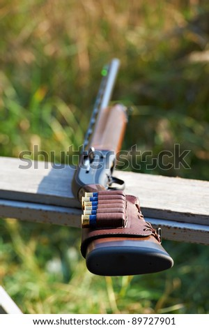 Shotgun with ammunition lying on the bench