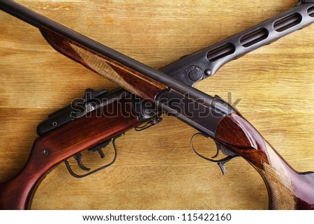 shotgun with assault rifle on wood