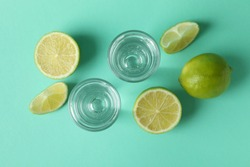 Shots and lime slices on mint background, top view