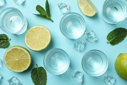 Shots, lime slices, mint and ice cubes on blue background, top view