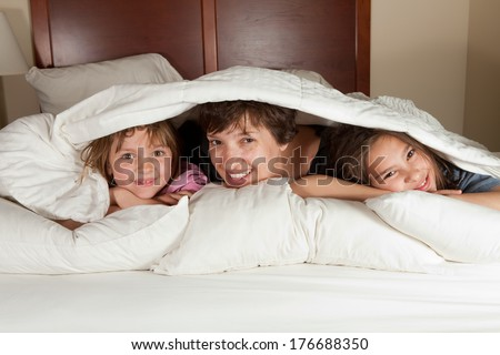 Shots of a mother and her two daughters waking up in bed with white linens part of a series - stock photo
