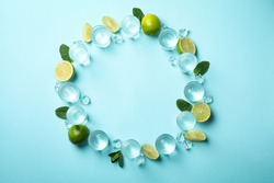 Shots of tequila or vodka, lime, mint and ice on blue background, top view