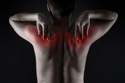 Shoulder blades pain, man with backache on black background, painful area highlighted in red