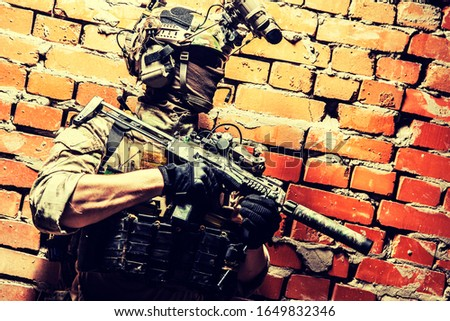 Shoulder portrait of army elite troops soldier, anti-terrorist tactical team, helmet with thermal imager, hiding face behind mask, armed assault rifle