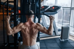 Shoulder pull down machine. Fitness man working out lat pulldown training at gym. Upper body strength exercise for the upper back.
