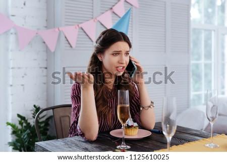 Shouting at boyfriend. Woman wearing striped blouse shouting at her boyfriend sitting at the table #1125610025