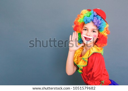 Shouting at camera concept. Little clown girl says hey you! #1051579682