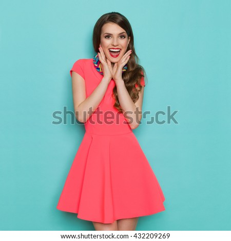 Shutterstock Shouting beautiful young woman in pink mini dress posing with hands on chin. Three quarter length studio shot on turquoise background.