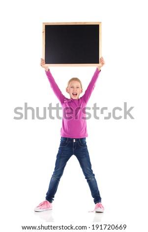 Shouting girl holding blackboard over her head. Full length studio shot isolated on white.