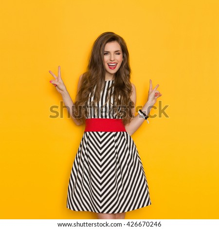 Shouting young woman in elegant striped dress winking and showing two finger or peace sign. Three quarter length studio shot on yellow background.