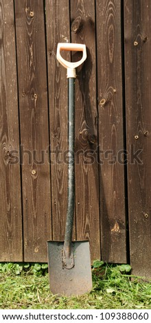 Shovel against wooden wall