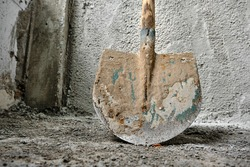 shovel in front of the recently made plastered wall by concrete. green colors exist on metal side of shovel. after construction works. photo taken low angle