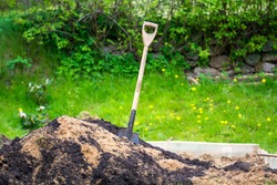 Shovel in pile of dirt and soil in a garden in spring